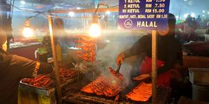 Woman serving grilled chicken butts at a night market in Kota Kinabalu, Malaysia (Photo: Adam Coulter/Cruise Critic)