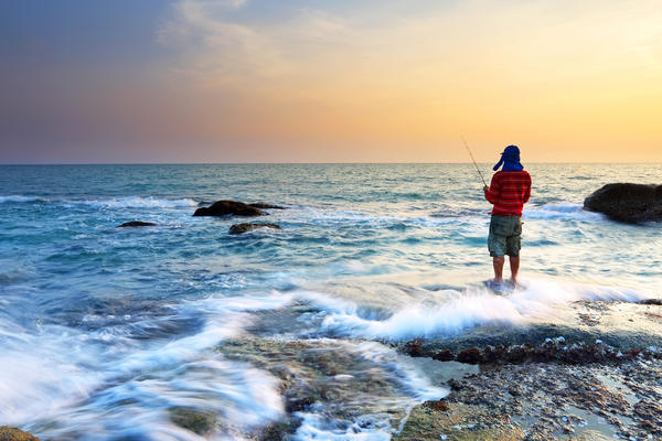 Man Fishing at Shore (Photo: isarescheewin/Shutterstock)