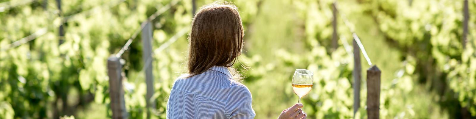 Woman Drinking Wine Observing Vineyard (Photo: RossHelen/Shutterstock)