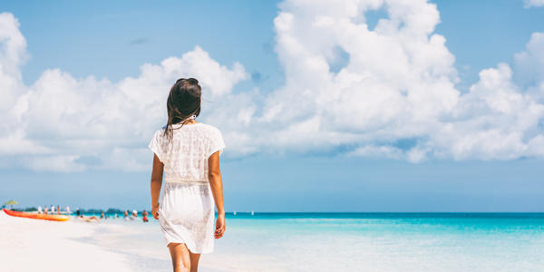 Woman walking on a beach in the Caribbean (Photo: Maridav/Shutterstock.com)