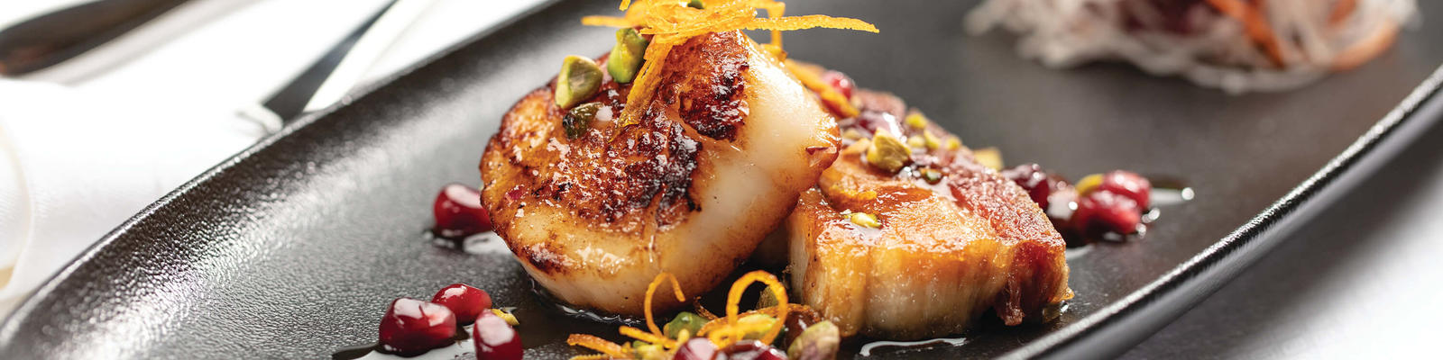 Close-up shot of plated seared diver scallops with cured pork belly confit and pomegranate seeds