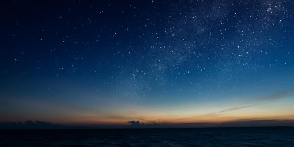 A starry night sky emerges during dusk at sea