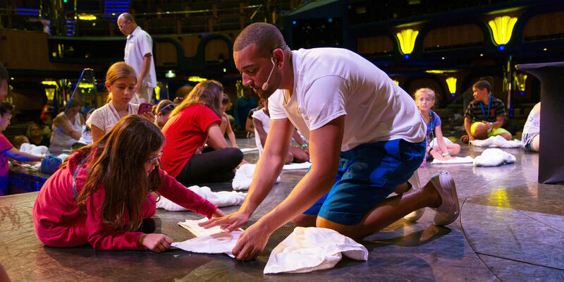 Cruise Director Teaching Children How to Create Towel Animals at the Towel Animal Theater (Photo: Carnival)