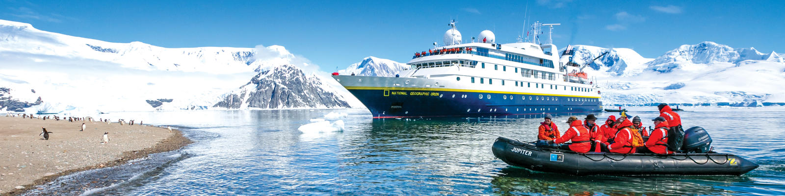 National Geographic Orion docked in Antarctica while a Zodiac full of passengers heads to a penguin-covered shore