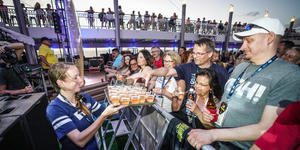 Woman passing out alcoholic drinks to fans at an onboard Bon Jovi concert