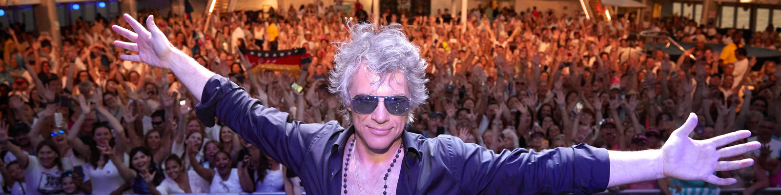 Jon Bon Jovi posing onstage, with hundreds of fans in the background, on the Bon Jovi cruise