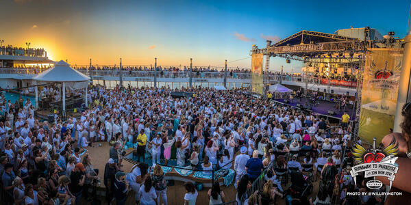A crowd of fans on the pool deck at sunset, awaiting Jon Bon Jovi's onboard performance