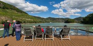 Group of older cruise passengers sitting in sun deck chairs, looking out at the Rhine River scenery