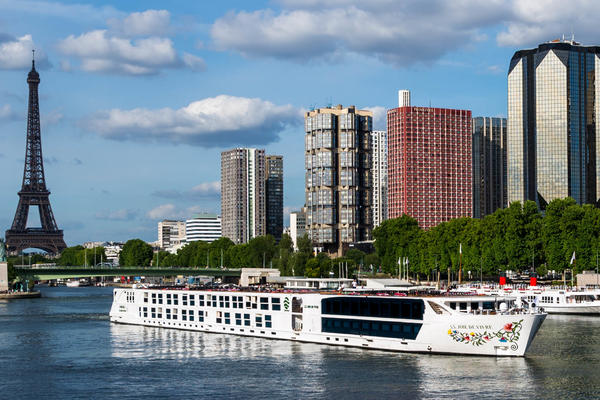 Shot of Joie de Vivre cruising the Seine River on a sunny day, with Eiffel Tower in the background