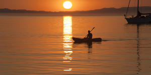 Photograph of a kayaker in the Sea of Cortez with the sun setting in the background - Photography by Stephen N Haynes via Shutterstock