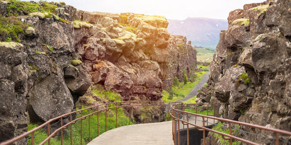 Photograph of a wooden foot bridge winding through Thingvellir National Park in Iceland - Photography by lkoimages via Shutterstock