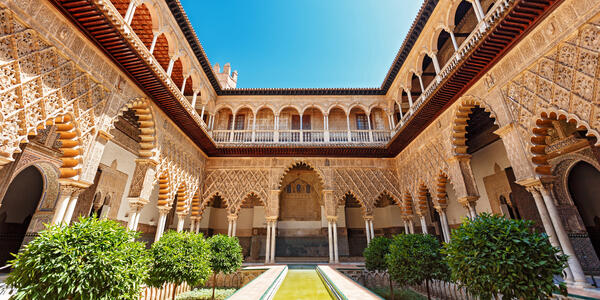 Photograph of the Palace of Alcazar, Famous Andalusian Architecture. Old Arab Palace in Seville, Spain. - Photography by Visual Intermezzo via Shutterstock