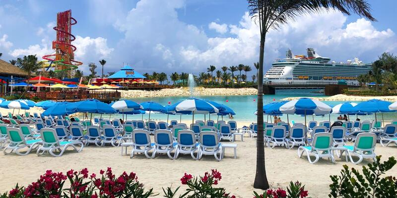 Blue beach chairs and umbrella with Royal Caribbean ship in the background at CocoCay
