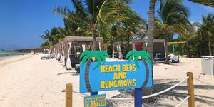 Beach Beds and Bungalows sign with bungalows in the background on CocoCay