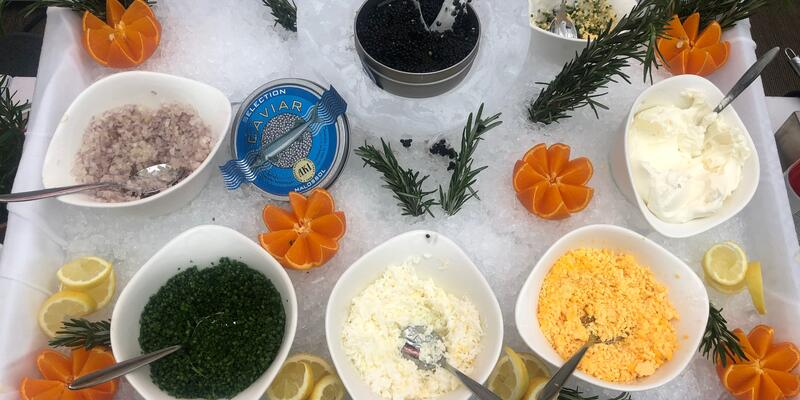 Overhead shot of a decorative caviar and condiment spread at the Pool Grill