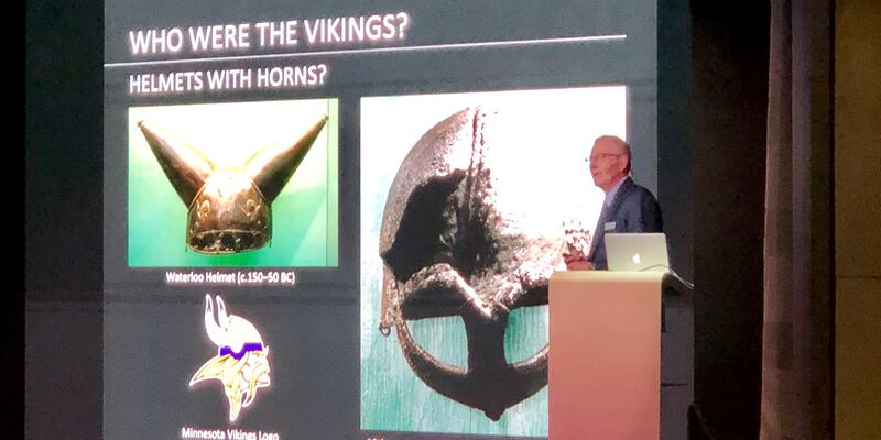 Photo of Viking Jupiter's Resident Historian giving a lecture on Vikings from the onstage theater podium