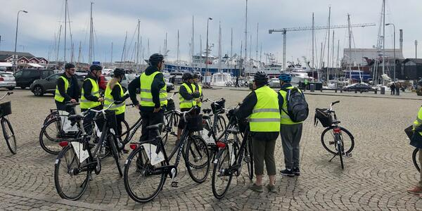 Group of bicyclists dressed in helmets and bright yellow jackets on a shore excursion in Skagen
