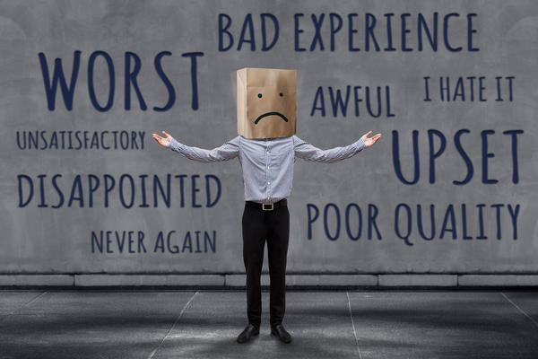 Image - Unhappy Businessman Client with Sadness Emotion Face on Paper Bag, Blurred Concrete Wall with Wording of Negative Reviews as background (Photo: Black Salmon/Shutterstock)