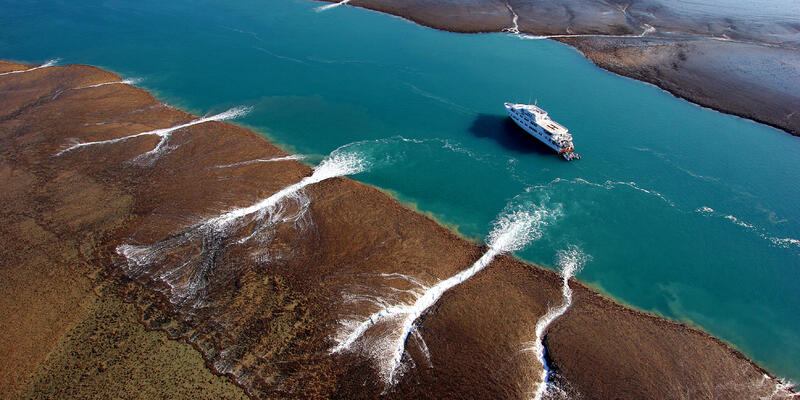 Image: Water rushes off Montgomery Reef during the fall of tide. True North II is anchored in a channel. (Photo: True North Adventure Cruises)