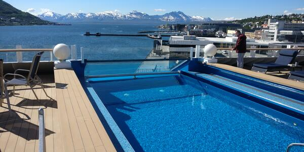The aft pool on Hurtigruten's new Roald Amundsen cruise ship with snow-capped mountains in Tromso, Norway, in the background