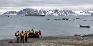 Expedition staff from Ponant's ship Le Boreal help cruisers off the Zodiac in Svalbard (Photo: Chris Gray Faust )