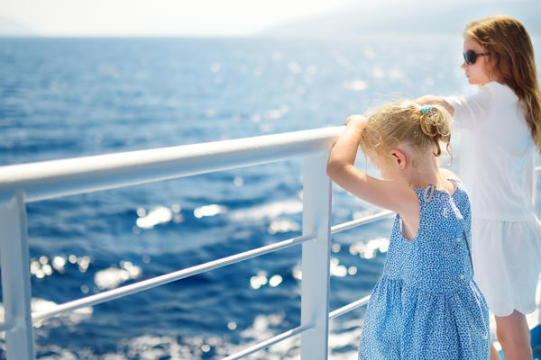 Young girls staring at the deep blue sea from a cruise ship railing
