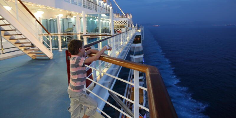 Little boy wearing shorts and striped shirt standing on deck of a ship at night