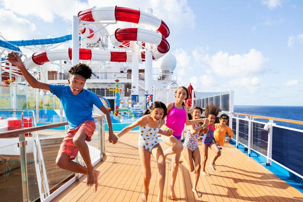Six kids of all ages holding hands and jumping on the Carnival Horizon pool deck