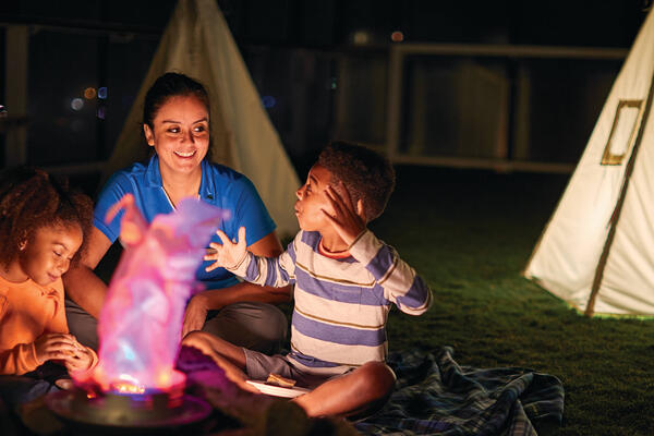Two kids and a camp counselor camping in front of a fake fire on a cruise ship