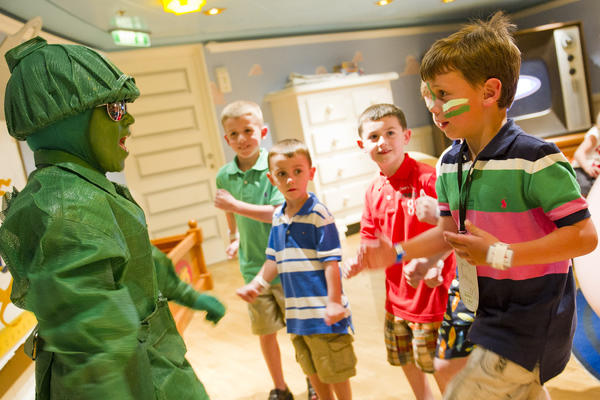 Group of kids interacting with an actor dressed as a toy soldier in Andy's Room, a Toy Story-theme room on Disney Cruise Line