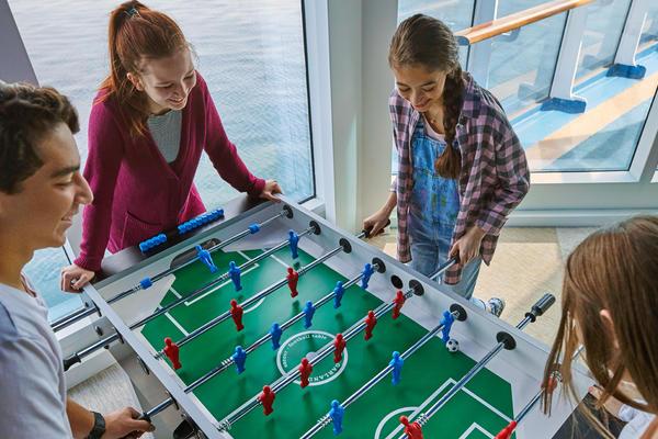 Four teens playing foosball on Caribbean Princess