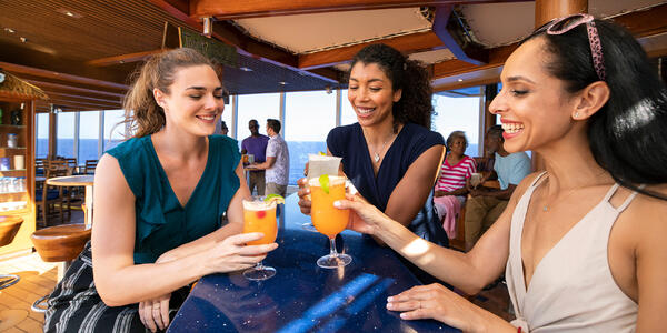 Three young women drinking and laughing on a cruise (Photo: Carnival Cruise Line)