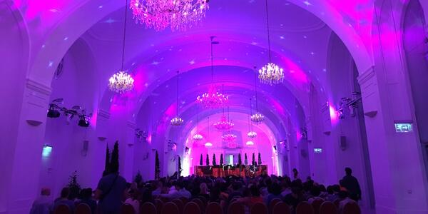 Dark-lit interior of a concert hall, with purple and pink links projected on the high ceilings