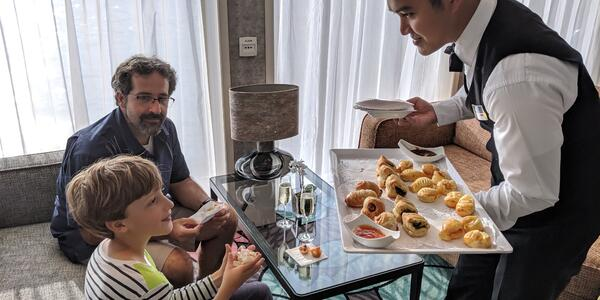 Waiter serving child and his father pastries on a river cruise ship