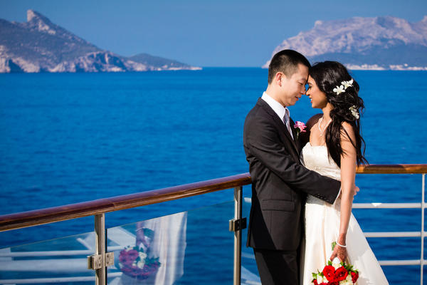Asian couple posing in wedding attire on the sun deck on Allure of the Seas