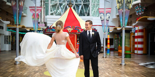 Man and woman in wedding attire dancing in front of the Boardwalk's Carousel on Oasis of the Seas