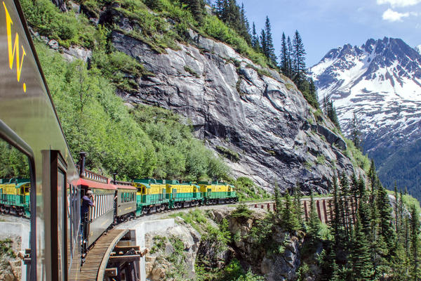 Exterior shot of White Pass and Yukon Railroad train bending around a mountain in Alaska