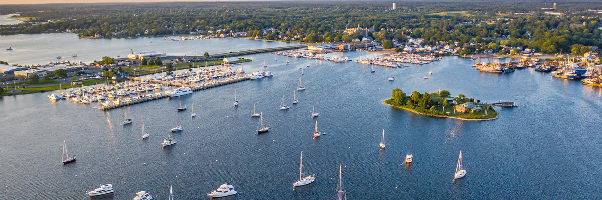 Boats Floating on Water in New Bedford Harbor, Massachusetts, With Lush Scenery in Distance (Photo: Matthew Botelho/Shutterstock)