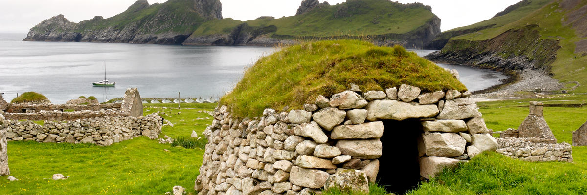A Stone Storage Hut, on the Isles of St Kilda, Scotland with a Vessel in the Water Near Scenic Mountains in the Background (Photo: Navin Mistry/Shutterstock)