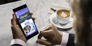 Close-up shot of business man using the OceanReady app on his smartphone while having a cappucino