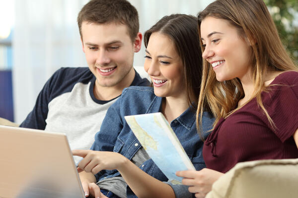 Three friends planning a cruise with a laptop using Cruise Critic (Photo: Antonio Guillem/Shutterstock)