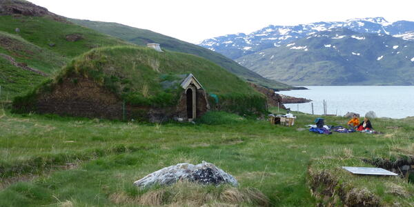 Travelers relax near one of the Reconstructed Viking Buildings at Brattahlid in Qassiarsuk, Greenland (Photo: Sarah Schlichter/Shutterstock)