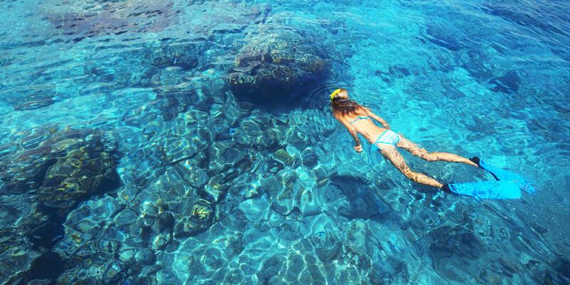 Woman Snorkeling in the Open Clear Blue Waters (Photo: Dudarev Mikhail/Shutterstock)