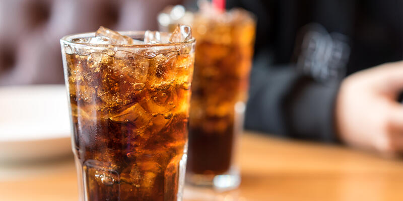Two glasses of dark soda on a tabletop