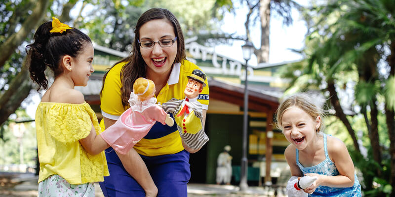 A woman and two smiling girls, laughing and playing with puppets on a Disney Cruise Port Adventures excursion