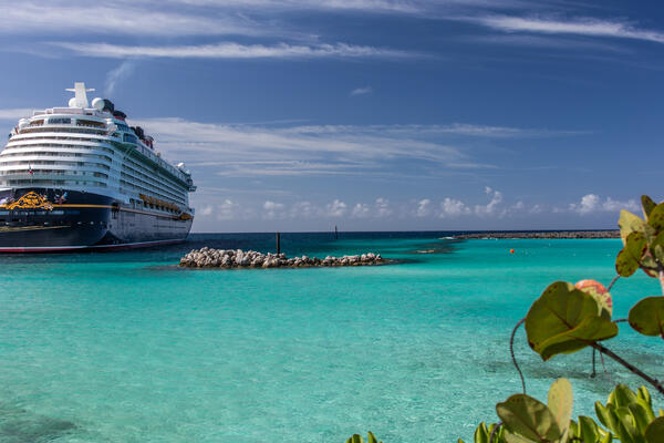 View of Disney Dream from Castaway Cay, with aqua Caribbean waters, a deep blue sky and white clouds
