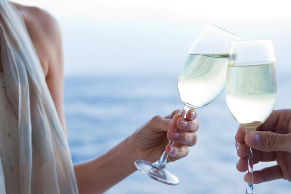 Close-up image of a man and woman toasting their Champagne glasses on a cruise ship deck, with ocean in the background