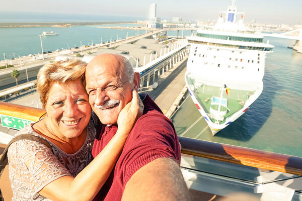Senior couple taking a selfie in front of their cruise ship docked in port