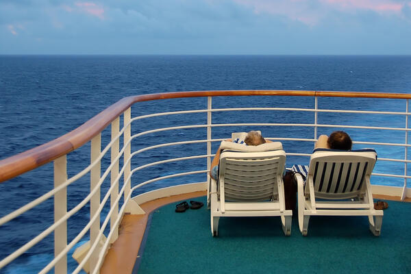 Older, retired couple lounging on deck chairs on a cruise ship sun deck