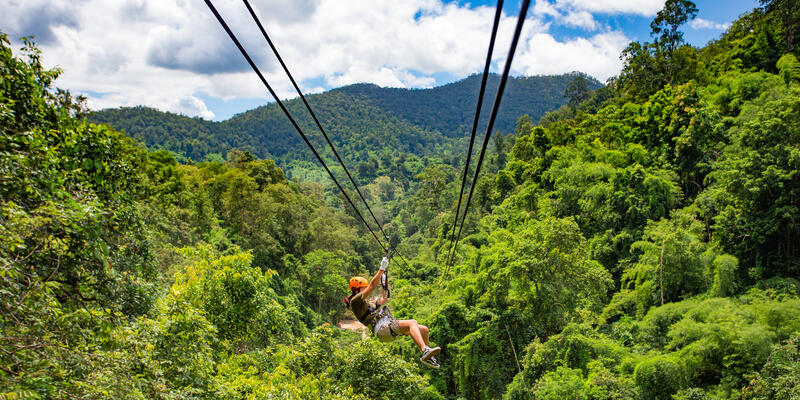 Woman in orange helmet ziplining through a lush forest in Chiang Mai, Thailand